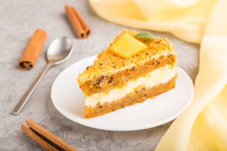 Homemade cake with persimmon and pumpkin and a cup of coffee on a gray concrete background with yellow textile. side view, close up, selective focus. Reklamní fotografie