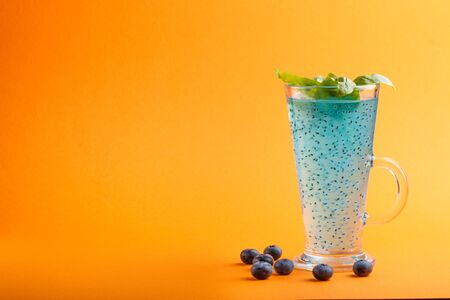 Glass of blueberry blue colored drink with basil seeds on orange background. Morninig, spring, healthy drink concept. Side view, selective focus, copy space. Reklamní fotografie