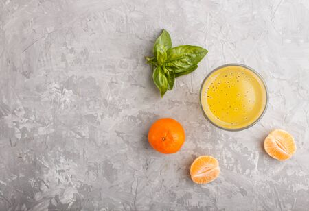 Glass of tangerine orange colored drink with basil seeds on a gray concrete background. Morninig, spring, healthy drink concept. Top view,  copy space, flat lay.