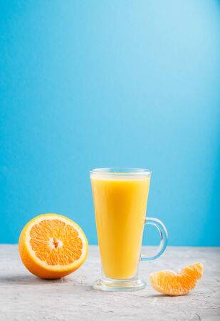 Glass of orange juice on a gray and blue background. Morninig, spring, healthy drink concept. Side view,  copy space.