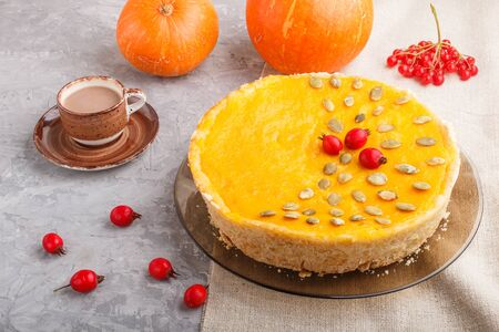 Traditional american sweet pumpkin pie decorated with hawthorn red berries and pumpkin seeds with cup of coffee on a gray concrete background. side view, close up.