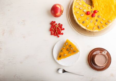 Traditional american sweet pumpkin pie decorated with hawthorn red berries and pumpkin seeds with cup of coffee on a white wooden background. top view, flat lay, copy space. Reklamní fotografie