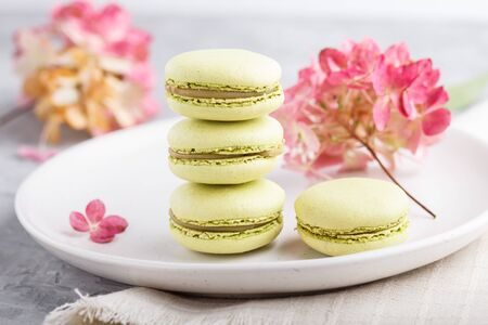 Green macarons or macaroons cakes on white ceramic plate on a gray concrete background and linen textile. side view, close up, selective focus.