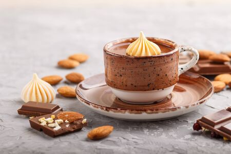 Cup of hot chocolate and pieces of milk chocolate with almonds on a gray concrete background. side view, close up, selective focus. Reklamní fotografie