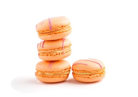 Orange macarons or macaroons cakes isolated on white