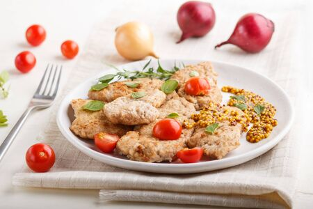 Fried pork chops with tomatoes and herbs on a white ceramic plate on a white wooden background and linen textile. side view, close up, selective focus.