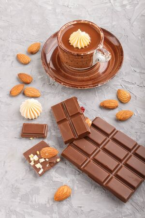 Cup of hot chocolate and pieces of milk chocolate with almonds on a gray concrete background. side view, close up.