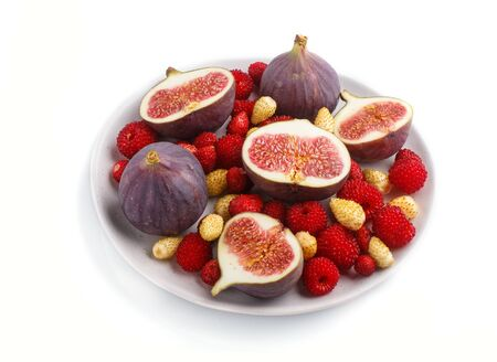 Fresh figs, strawberries and raspberries on white ceramic plate isolated on white background. side view, close up.