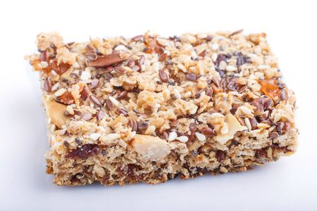 Homemade granola from oat flakes, dates, dried apricots, raisins, nuts isolated on white background. Side view, close up, macro. Reklamní fotografie