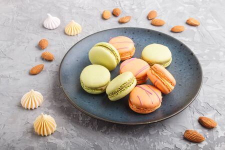 Orange and green macarons or macaroons cakes on blue ceramic plate on a gray concrete background. side view, close up. Reklamní fotografie