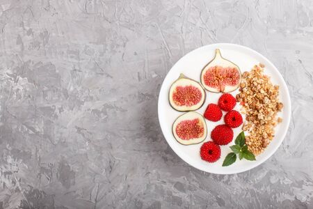 Yoghurt with raspberry, granola and figs in white plate on a gray concrete background. top view, flat lay, copy space.