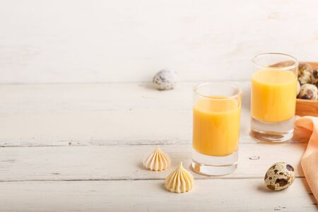 Sweet egg liqueur in glass with quail eggs and meringues on white wooden Reklamní fotografie
