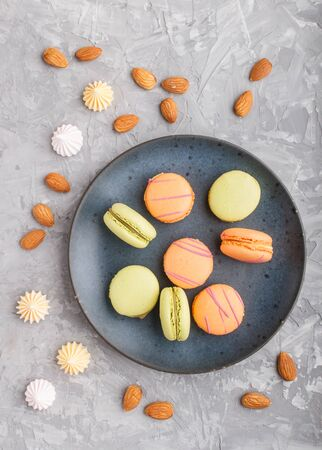 Orange and green macarons or macaroons cakes on blue ceramic plate on a gray concrete