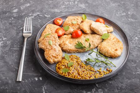 Fried pork chops with tomatoes and herbs on a gray ceramic plate on a black concrete background. side view, close up. Reklamní fotografie