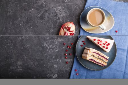 Homemade layered cake with pomegranate jam and a cup of coffee on a black concrete background and blue textile. top view, flat lay, copy space. Reklamní fotografie