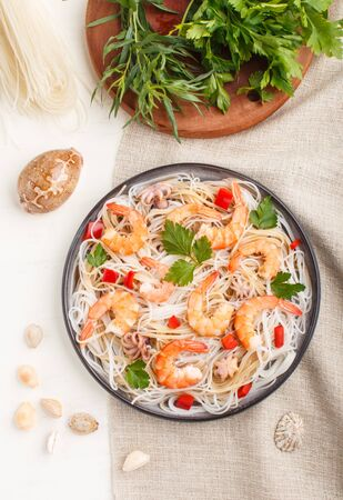 Rice noodles with shrimps or prawns and small octopuses on gray ceramic plate on a white wooden background and linen textile. Top view, flat lay, close up.