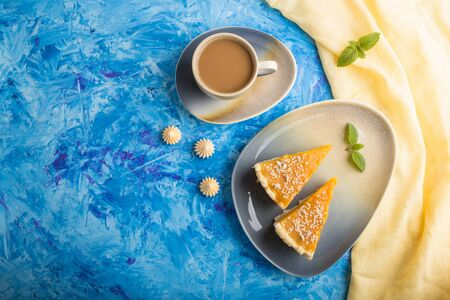Two pieces of traditional american pumpkin pie with cup of coffee on a blue concrete background and yellow textile. top view, flat lay, copy space, contrast. Reklamní fotografie