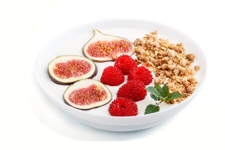 Yoghurt with raspberry, granola and figs in white plate isolated on white background. side view, close up.