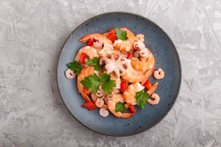 Boiled shrimps or prawns and small octopuses with herbs on a blue ceramic plate on a gray concrete background. Top view, flat lay, close up.