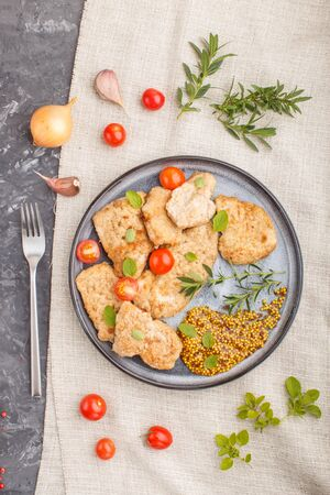 Fried pork chops with tomatoes and herbs on a gray ceramic plate on a black concrete Reklamní fotografie