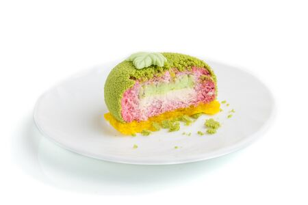 Green mousse cake with pistachio and strawberry cream isolated on white background. side view, close up.