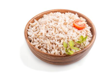 Unpolished rice porridge in wooden bowl isolated on white background. side view, close up.