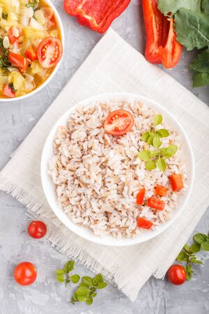 Unpolished rice porridge with stewed vegetables and oregano in white bowl on a gray concrete background and linen textile. Top view, flat lay, close up. Reklamní fotografie