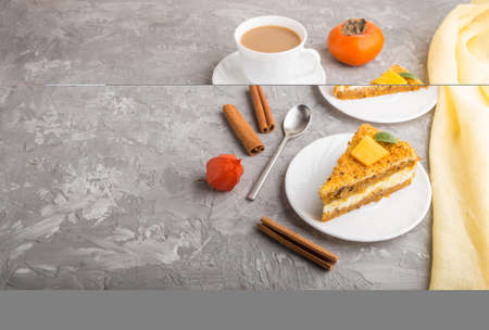 Homemade cake with persimmon and pumpkin and a cup of coffee on a gray concrete background with yellow textile. side view, copy space, close up. Stock Photo