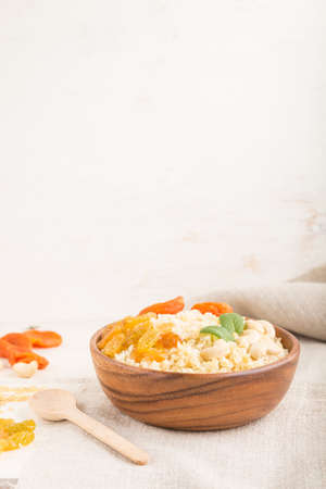 Bulgur porridge with dried apricots, raisins and cashew in wooden bowl on a white wooden background and linen textile. Side view, copy space, selective focus. Turkish traditional cuisine.
