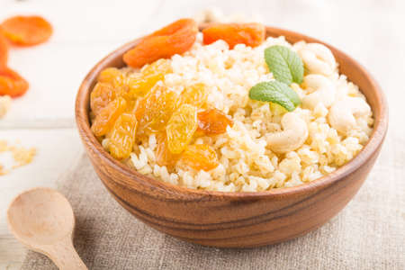 Bulgur porridge with dried apricots, raisins and cashew in wooden bowl on a white wooden background and linen textile. Side view, close up, selective focus. Turkish traditional cuisine.