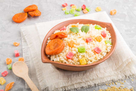 Bulgur porridge with dried apricots and candied fruits in clay bowl on a gray concrete background and linen textile. Side view, close up. Turkish traditional cuisine.