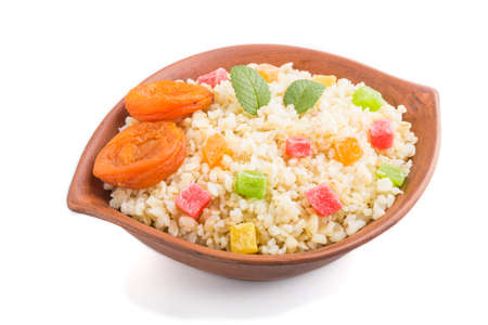 Bulgur porridge with dried apricots and candied fruits in clay bowl isolated on white background. Side view, close up. Turkish traditional cuisine.