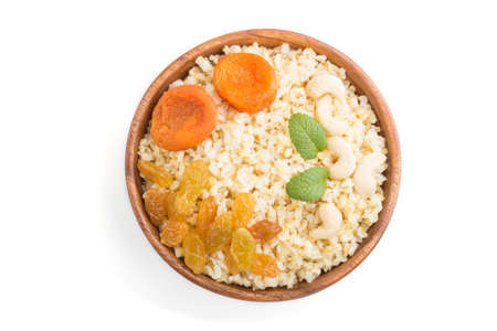 Bulgur porridge with dried apricots, raisins and cashew in wooden bowl isolated on white background. Top view, flat lay, close up. Turkish traditional cuisine.