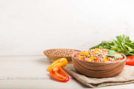 Buckwheat porridge with vegetables in wooden bowl on a white wooden background and linen textile. Side view, copy space, selective focus. Russian traditional cuisine.