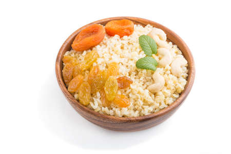 Bulgur porridge with dried apricots, raisins and cashew in wooden bowl isolated on white background. Side view, close up. Turkish traditional cuisine. 免版税图像