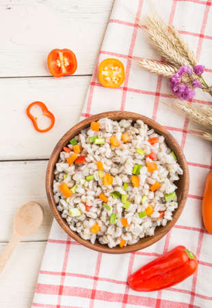 Pearl barley porridge with vegetables in wooden bowl on a white wooden background and linen textile. Top view, flat lay, close up. Russian traditional cuisine. 免版税图像