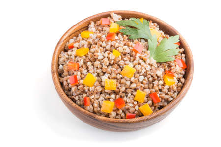 Buckwheat porridge with vegetables in wooden bowl isolated on white background. Side view, close up. Russian traditional cuisine. 免版税图像