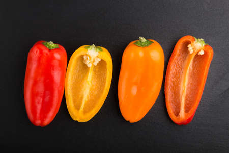 yellow, red, orange sweet peppers on a black slate background. top view, flat lay, close up.