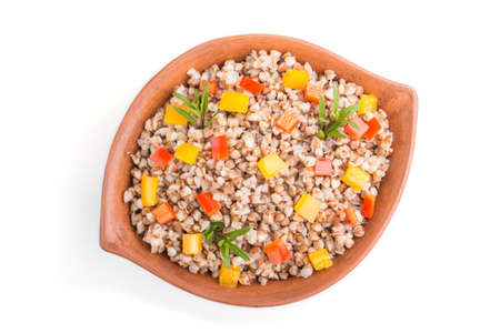 Buckwheat porridge with vegetables in clay bowl isolated on white background. Top view, flat lay, close up. Russian traditional cuisine. 免版税图像