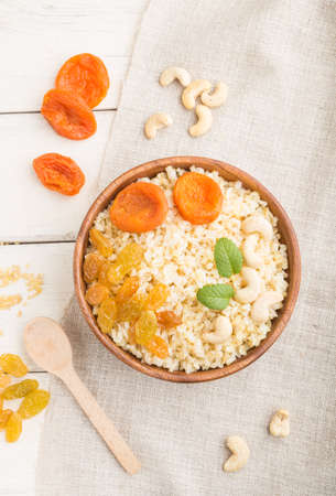 Bulgur porridge with dried apricots, raisins and cashew in wooden bowl on a white wooden background and linen textile. Top view, flat lay, close up. Turkish traditional cuisine.