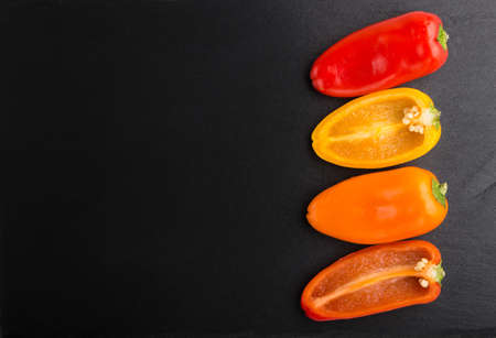 yellow, red, orange sweet peppers on a black slate background. top view, copy space, flat lay, close up.