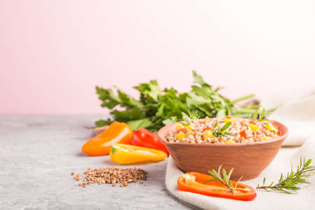 Buckwheat porridge with vegetables in clay bowl on a gray and pink background and linen textile. Side view, selective focus, copy space. Russian traditional cuisine.