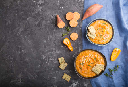 Sweet potato or batata cream soup with sesame seeds and snacks in blue ceramic bowls on a black concrete background with blue linen textile. top view, flat lay, copy space. 免版税图像