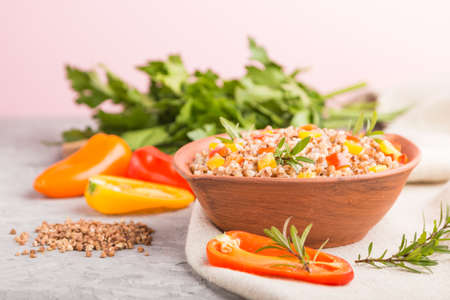 Buckwheat porridge with vegetables in clay bowl on a gray concrete background and linen textile. Side view, selective focus, close up. Russian traditional cuisine.