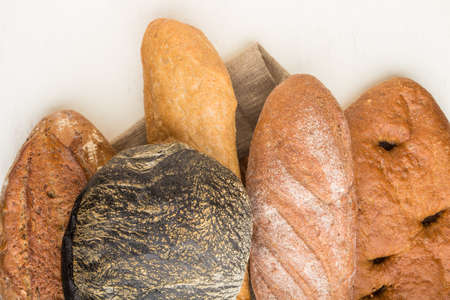 Different kinds of fresh baked bread on a white wooden background. top view, flat lay, close up. 免版税图像