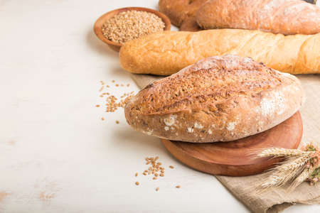 Different kinds of fresh baked bread on a white wooden background. side view, close up, copy space. 免版税图像