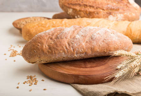 Different kinds of fresh baked bread on a white wooden background. side view, close up, selective focus.