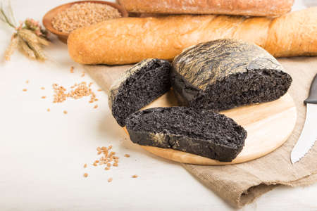 Sliced black bread with different kinds of fresh baked bread on a white wooden background. side view, close up, copy space. 免版税图像