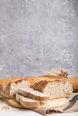 Sliced bread with different kinds of fresh baked bread on a gray concrete background. side view, close up, selective focus.