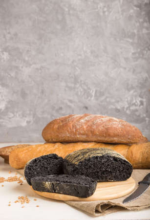 Sliced black bread with different kinds of fresh baked bread on a gray concrete background. side view, close up, selective focus. 免版税图像